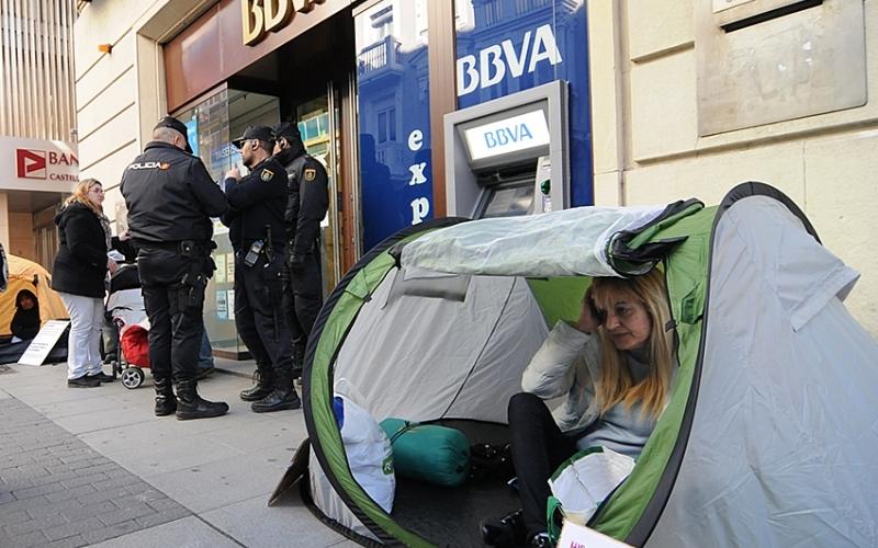 """Demasiado tarde: con la gente mirando, ya solo queda """"proteger"""" la entrada del banco."""